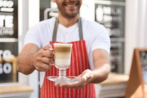 Smiling waiter standing in entrance of coffee shop