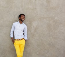 confident african american man leaning on wall laughing