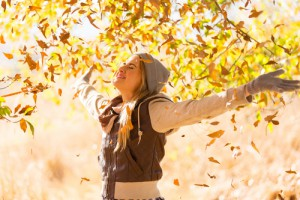 autumn leaves falling on happy young woman