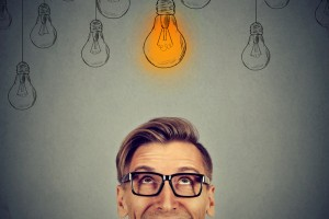 man in glasses looking up at bright idea light bulb above head